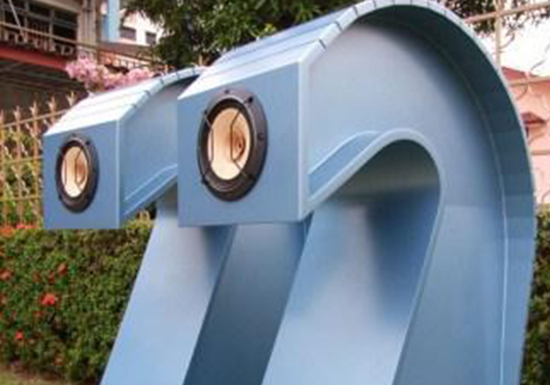 A pair of curved, wood speakers